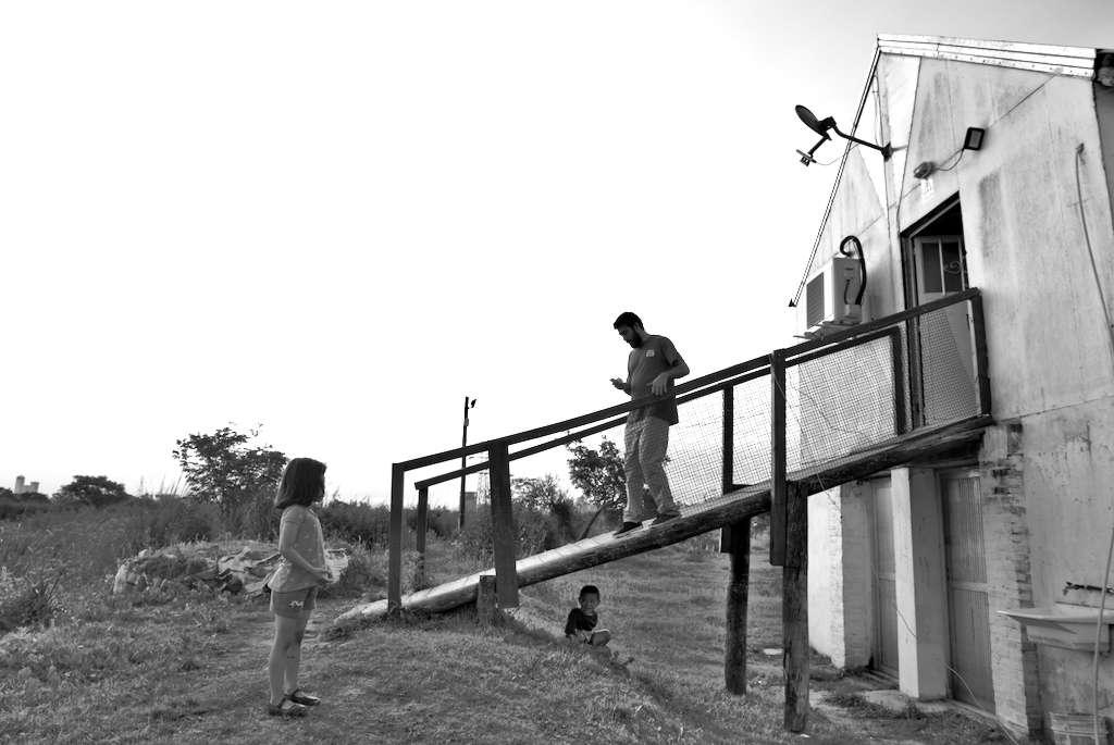 Uno de los docentes del bachillerato popular baja por la pasarela del Centro Cultural y Comunitario Casa de los Talleres. Abajo de la misma se ve a un niño y sobre la izquierda de la foto una niña