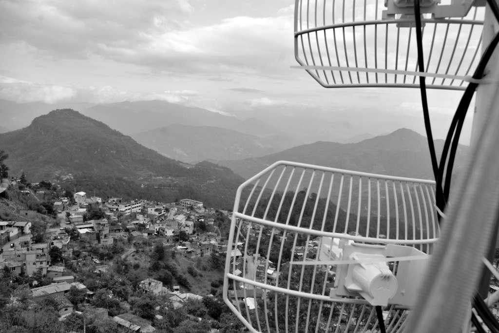 En primer plano la antena de telefonía comunitaria. Abajo se observan las casas de Santa María Alotepec, Oaxaca. Al fondo las montañas