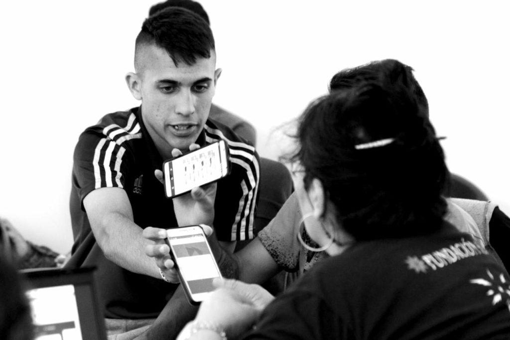 Un jóven participando del taller de radios, le muestra a una mujer una configuración en su móvil
