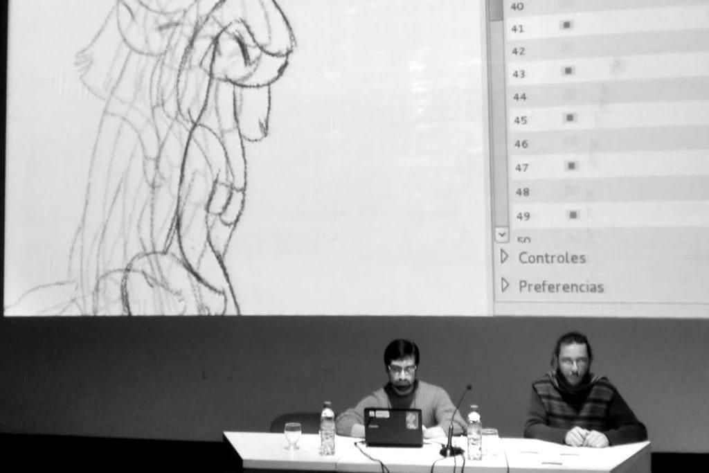 Dos varones sentados mirando al frente durante una presentación en un auditorio. Detrás se ve proyectada en la pantalla un frame de animación en MyPaint